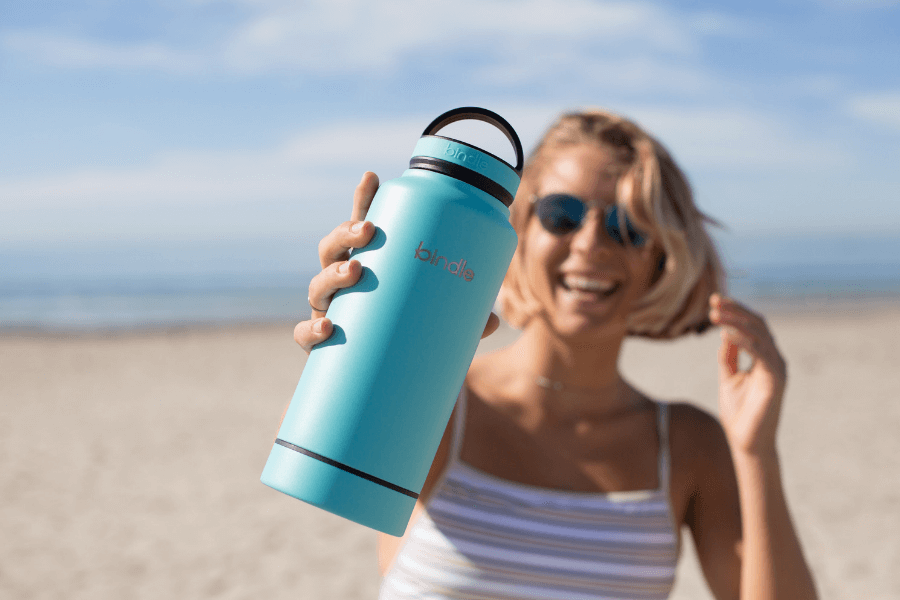 Woman on Beach with Steel Water Bottle. Try to use steel water bottle to reduce plastic use.