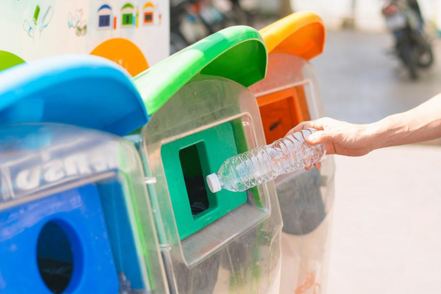 Bottle being placed into recycling bins. Reduce, reuse and recycle is part of the sustainability in the workplace method.